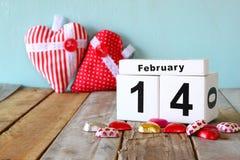 14. Februar hölzerner Weinlesekalender mit bunten Herzformschokoladen auf Holztisch Selektiver Fokus Lizenzfreie Stockfotografie