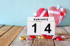 14. Februar hölzerner Weinlesekalender mit bunten Herzformschokoladen auf Holztisch Selektiver Fokus Lizenzfreies Stockbild