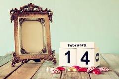 14. Februar hölzerner Weinlesekalender mit bunten Herzformschokoladen nahe bei leerem Weinleserahmen auf Holztisch Lizenzfreies Stockbild