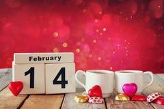 14. Februar hölzerner Weinlesekalender mit bunten Herzformschokoladen nahe bei Paarschalen auf Holztisch Selektiver Fokus Lizenzfreie Stockbilder