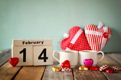 14. Februar hölzerner Weinlesekalender mit bunten Herzformschokoladen nahe bei Paarschalen auf Holztisch Selektiver Fokus Lizenzfreie Stockfotos