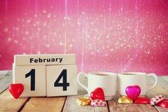 14. Februar hölzerner Weinlesekalender mit bunten Herzformschokoladen nahe bei Paarschalen auf Holztisch Selektiver Fokus Stockbild