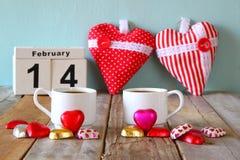 14. Februar hölzerner Weinlesekalender mit bunten Herzformschokoladen nahe bei Paarschalen auf Holztisch Selektiver Fokus Lizenzfreies Stockfoto