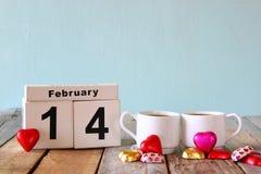 14. Februar hölzerner Weinlesekalender mit bunten Herzformschokoladen nahe bei Paarschalen auf Holztisch Selektiver Fokus Lizenzfreie Stockfotografie