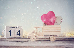 14. Februar hölzerner Weinlesekalender mit hölzernem Spielzeuglastwagen mit Herzen vor Tafel Stockfoto