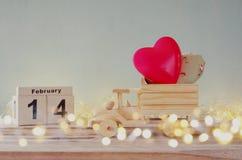 14. Februar hölzerner Weinlesekalender mit hölzernem Spielzeuglastwagen mit Herzen vor Tafel Lizenzfreies Stockbild