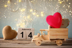 14. Februar hölzerner Weinlesekalender mit hölzernem Spielzeuglastwagen mit Herzen vor Tafel Lizenzfreies Stockfoto