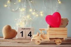 14. Februar hölzerner Weinlesekalender mit hölzernem Spielzeuglastwagen mit Herzen vor Tafel Stockfotografie