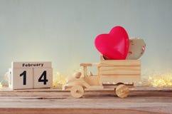 14. Februar hölzerner Weinlesekalender mit hölzernem Spielzeuglastwagen mit Herzen vor Tafel Stockbild