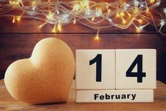 14. Februar hölzerner Weinlesekalender nahe bei Herzen auf Holztisch Weinlese gefiltert Stockbilder