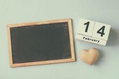 14. Februar hölzerner Weinlesekalender und hölzernes Herz nahe bei Tafel auf hölzernem hellblauem Hintergrund Stockfotografie