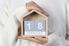 18. Februar im Kalender das Mädchen hält einen hölzernen Kalender Welttag für den Schutz von Marine Mammals Lizenzfreie Stockbilder