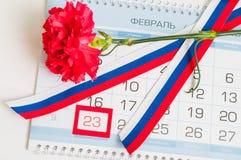 23. Februar Postkarte Rote Gartennelke, russische dreifarbige Flagge und Kalender mit gestaltetem Datum am 23. Februar Stockfotografie