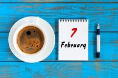 7. Februar Tag 7 des Monats, der Draufsicht über Kalender und der MorgenKaffeetasse am Arbeitsplatzhintergrund Blume im Schnee Lizenzfreie Stockfotos