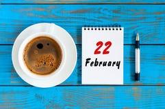 22. Februar Tag 22 des Monats, der Draufsicht über Kalender und der MorgenKaffeetasse am Arbeitsplatzhintergrund Blume im Schnee Stockfotografie