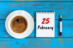 25. Februar Tag 25 des Monats, der Draufsicht über Kalender und der MorgenKaffeetasse am Arbeitsplatzhintergrund Blume im Schnee Lizenzfreies Stockfoto