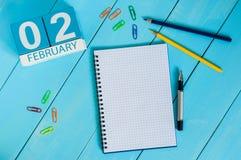 2. Februar Tag 2 des Monats, Kalender auf hölzernem Hintergrund Blume im Schnee Leerer Platz für Text Lizenzfreies Stockfoto