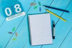 8. Februar Tag 8 des Monats, Kalender auf hölzernem Hintergrund Blume im Schnee Leerer Platz für Text Lizenzfreie Stockbilder