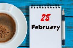 28. Februar Tag 28 des Monats, Kalender im Notizblock auf hölzernem Hintergrund nahe Morgenschale mit Kaffee Blume im Schnee Stockfotografie