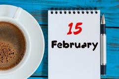 15. Februar Tag 15 des Monats, Kalender im Notizblock auf hölzernem Hintergrund nahe Morgenschale mit Kaffee Blume im Schnee Lizenzfreie Stockfotos