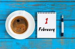 1. Februar Tag 1 des Monats, Loseblattkalender mit Stift und MorgenKaffeetasse am Arbeitsplatzhintergrund Blume im Schnee Lizenzfreie Stockfotos