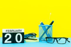 20. Februar Tag 20 von Februar-Monat, Kalender auf gelbem Hintergrund mit Büroartikel Blume im Schnee Lizenzfreies Stockfoto