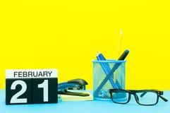 21. Februar Tag 21 von Februar-Monat, Kalender auf gelbem Hintergrund mit Büroartikel Blume im Schnee Lizenzfreies Stockfoto