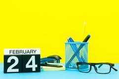 24. Februar Tag 24 von Februar-Monat, Kalender auf gelbem Hintergrund mit Büroartikel Blume im Schnee Lizenzfreie Stockfotos