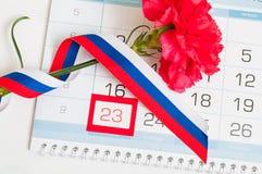 23. Februar - Verteidiger der Vaterland-Tageskarte Rote Gartennelke, russische Flagge und Kalender mit gestaltetem Datum am 23. F Stockfotografie