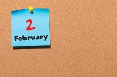 2 februari Dag 2 van maand, kalender op cork de achtergrond van de berichtraad Bloem in de sneeuw Lege ruimte voor tekst De idyll Stock Foto