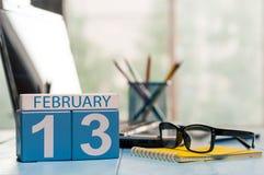 13 februari Dag 13 van maand, kalender op de achtergrond van de ontwerperwerkplaats Bloem in de sneeuw Lege ruimte voor tekst De  Stock Afbeeldingen