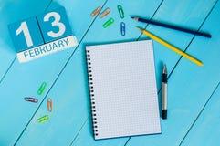 13 februari Dag 13 van maand, kalender op houten achtergrond Bloem in de sneeuw Lege ruimte voor tekst De idylle van de zomer Stock Foto's