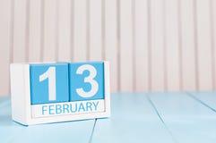 13 februari Dag 13 van maand, kalender op houten achtergrond Bloem in de sneeuw Lege ruimte voor tekst De idylle van de zomer Royalty-vrije Stock Foto