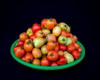 22, Februari 2017 Dalat--tomatenvruchten op groene plastic mand, zwarte achtergrond Stock Foto