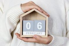 06 februari in de kalender het meisje houdt een houten kalender De dag van de internationale barman Stock Afbeelding