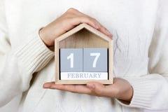 17 februari in de kalender het meisje houdt een houten kalender Willekeurige handelingen van vriendelijkheidsdag Stock Foto