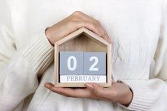 Februari 2 i kalendern flickan rymmer en träkalender Groundhog dag, världsvåtmarkdag Royaltyfri Bild
