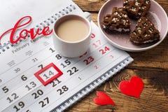 Februari 14 kalender Valentin dagbegrepp, röda hjärtor, ordförälskelsen och en kopp kaffe arkivfoton