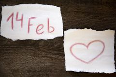 Februari 14 och hjärtan dras i röd blyertspenna på ett ark av papper, allt lokaliseras på ett träbräde royaltyfria bilder