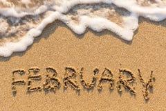 Februari - ord som dras på sandstranden med den mjuka vågen Arkivfoto