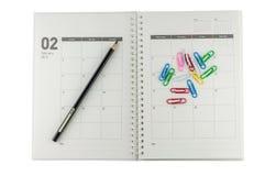 2014 Februari organisatör med blyertspennan & gem. arkivbild