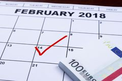 Februari 14 som markeras på kalendern och pengarna som läggs undan för gåvor Arkivfoto