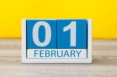 Februari 1st dag 1 av den februari månaden, kalender på gul arbetsplatsbakgrund vinter för blommasnowtid Arkivfoton