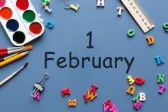 Februari 1st dag 1 av den februari månaden, kalender på skolpojke eller skolflickatabell, blå bakgrund vinter för blommasnowtid Arkivbild