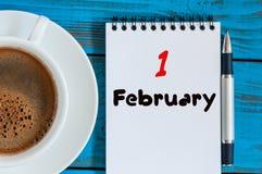 Februari 1st dag 1 av månaden, kalender i notepad på träbakgrund nära morgonkoppen med kaffe vinter för blommasnowtid tomt Arkivfoton