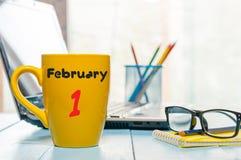 Februari 1st dag 1 av månaden, kalender på morgonte eller kaffekopp på arbetsplatsbakgrund vinter för blommasnowtid Töm utrymme Fotografering för Bildbyråer