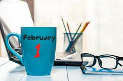 Februari 1st dag 1 av månaden, kalender på morgonte eller kaffekopp på arbetsplatsbakgrund vinter för blommasnowtid Töm utrymme Arkivbilder