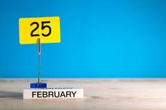 Februari 25th Dag 25 av den februari månaden, kalender på liten etikett på blå bakgrund vinter för blommasnowtid Tomt avstånd för Arkivfoto