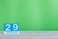 Februari 29th Skära i tärningar kalendern för februari 29 på träarbetsplats med med grön bakgrund och töm utrymme för text Royaltyfri Fotografi