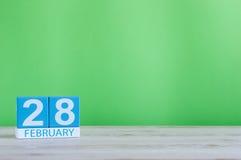 Februari 28th Skära i tärningar kalendern för februari 28 på träskrivbordet med grön bakgrund och töm utrymme för text Att inte h Royaltyfri Bild